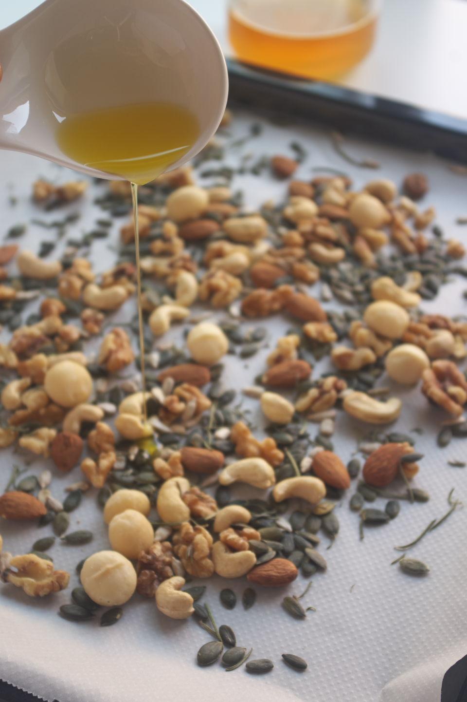 Añadiendo aceite a frutos secos en bandeja de horno