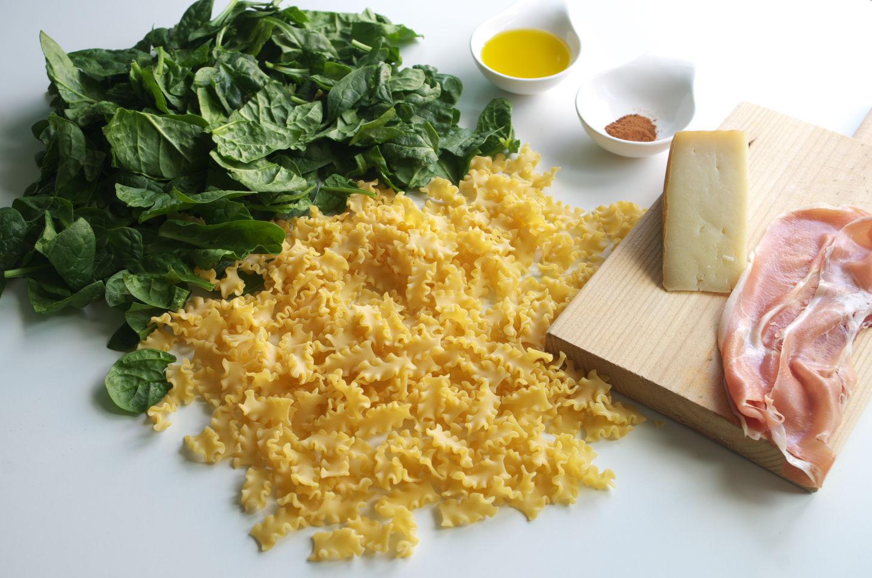 Ingredientes para receta de pasta mafalda corta con espinacas y jamón. Se ve Aceite de Oliva Virgen Extra, nuez moscada, queso de oveja curada, espinacas, la pasta y jamón