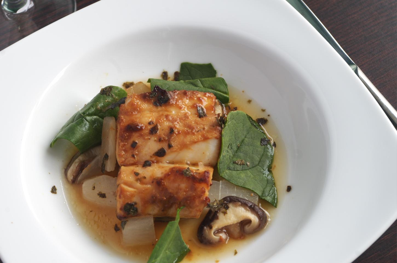 Vista cenital de plato con bacalao con setas y nabo daikon