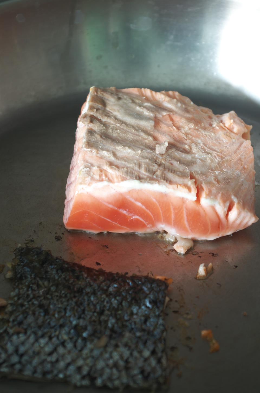 Cocinando salmón y su piel aparte para receta de Primer plano de salmón con salsa de arroz integral en plato