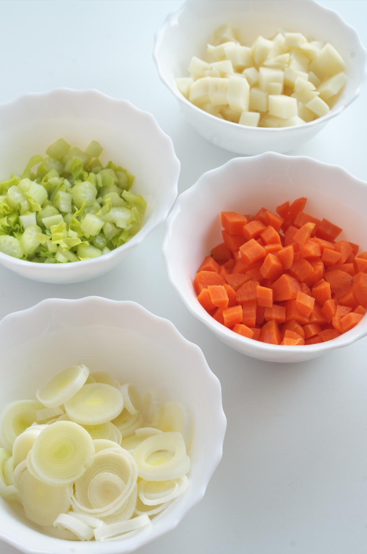 Puerro, zanahoria, apio y patata cortada para receta de sopa de arroz, setas y verduras